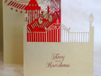 Photo of Red and gold laser cut layered wedding card with fort