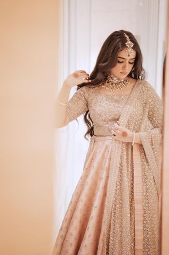 Candid shot of a bride dressed in a pastel lehenga.