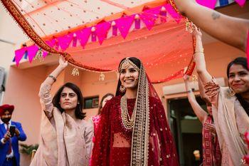 Bride making an entry under a dupatta.