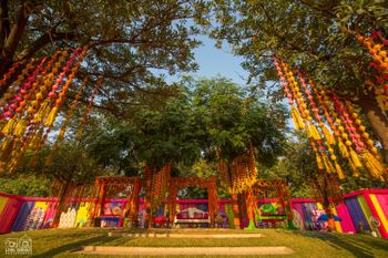 Photo of Mehendi decor with hanging gota strings from trees