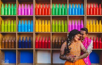 Photo of Colourful painted bottles as backdrop for mehendi