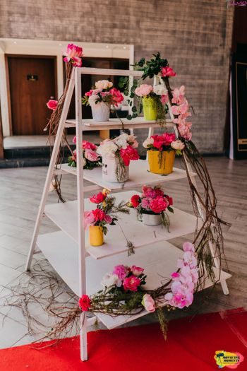 Ladder decorated with a bunch of floral centerpieces.