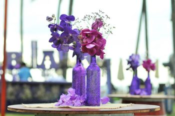 Photo of Purple bottle and flower centerpiece with flowers