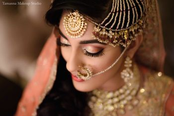 Photo of Gold bridal look with jhoomer nath and maangtikka