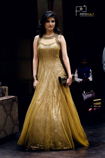 floor length shimmery gold gown with net overlay