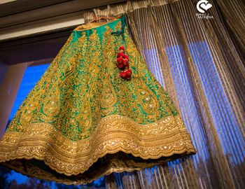 Green and gold lehenga on hanger in room