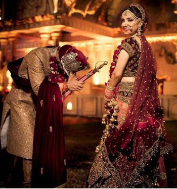 Photo of wine and gold bridal lehenga