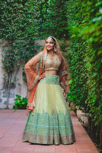 Photo of lime green and gold lehenga with coral dupatta