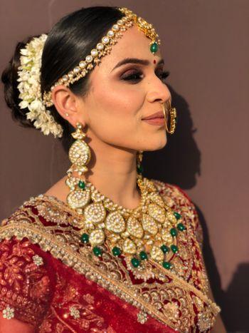 Bride wearing polki jewellery with her velvet lehenga.