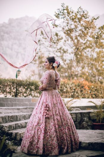 Photo of Bride dressed in a baby pink lehenga.