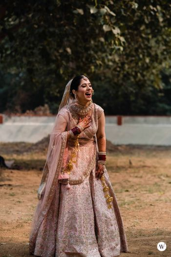 Photo of Candid bridal shot on wedding day with a bride in a pastel lehenga