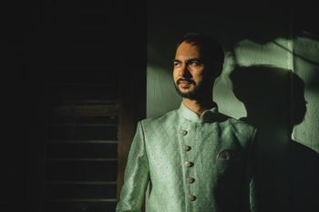 Groom dressed in a mint green sherwani.