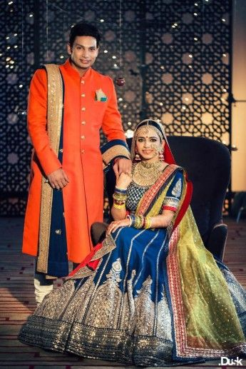 Photo of orange sabyasachi sherwani with blue dupatta