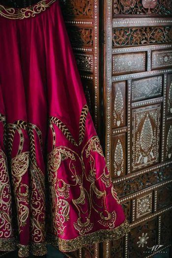 Photo of Magenta bridal lehenga with zardozi work on hanger
