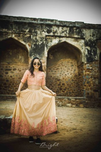 bride wearing peach and yellow lehenga with sneakers
