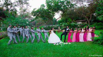 Couple playing tug of war with bridesmaids and groomsmen