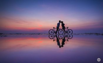 Pre wedding shoot with cycles on beach during sunset