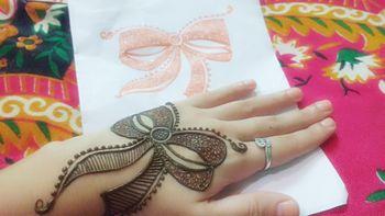 Photo of Bow shaped mehendi on back of the hand