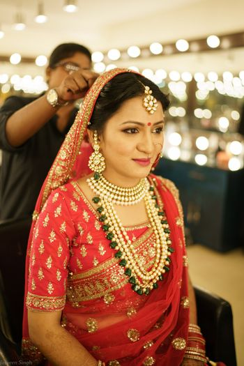 Contrasting green and gold jewellery with red bridal lehenga