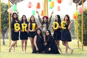 Photo of Bride with bridesmaids and bride balloons with black and gold theme
