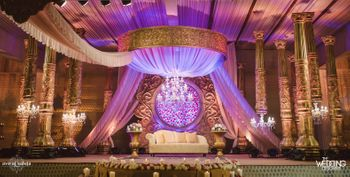 Photo of Opulent and grand stage decor in gold with pink flower wall