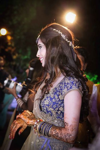 Wavy hairstyle with floral band for bride on sangeet