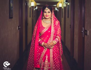 Photo of Bride in raspberry pink lehenga with contrasting green jewellery