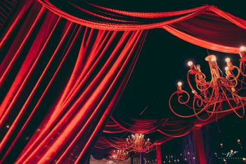 Glam red decor theme with wrought iron chandeliers