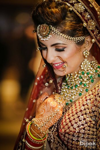 Bride wearing necklace with green beads and pearl maangtikka