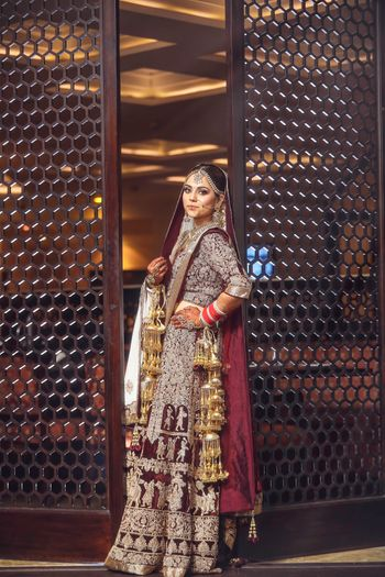 Photo of Winter wedding lehenga in maroon with royal motifs