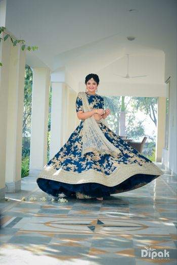 Photo of Bride twirling in blue lehenga with floral motifs
