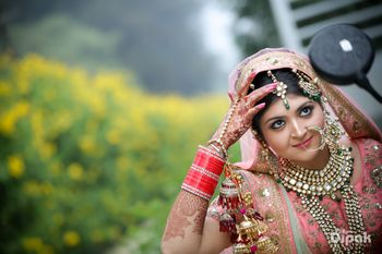 Photo of Contrasting jewellery with green with light pink lehenga
