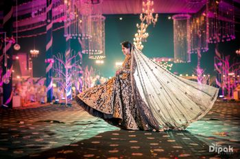 Bride twirling in dark lehenga with long dupatta