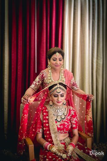 Mom placing dupatta on brides head
