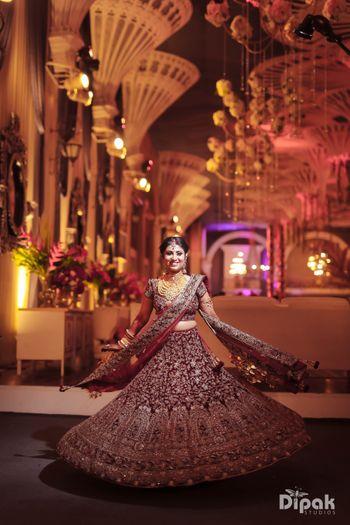 Bride twirling in maroon bridal lehenga