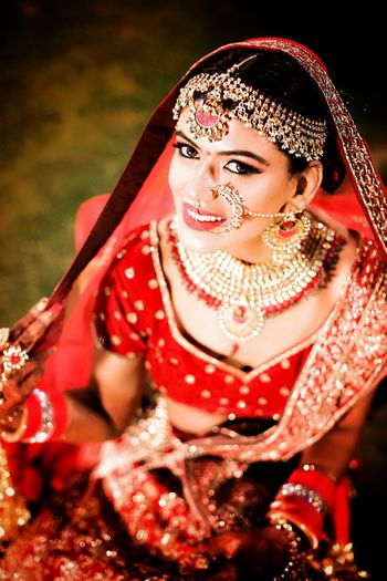 Bridal jewellery with mathapatti nath and choker necklace with red beads