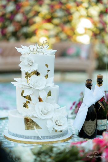 Three-tiered white wedding cake with florals.