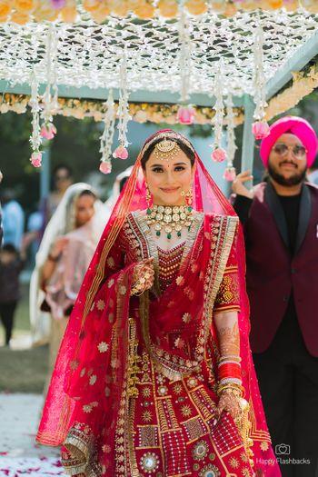 Bride making an entry under a phoolon ki chaadar.