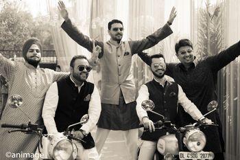 Photo of fun groom entry with groomsmen on bike