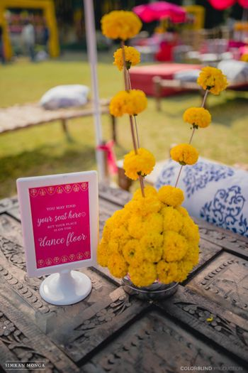 Photo of Mehendi table setting with floral centerpiece and dance floor sign