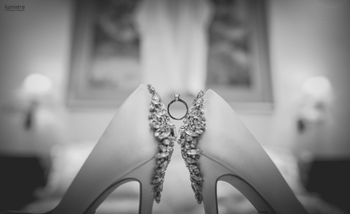 Black and white photo of ring between bridal shoes
