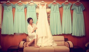 Bride getting ready with hers and bridesmaids dresses on hanger