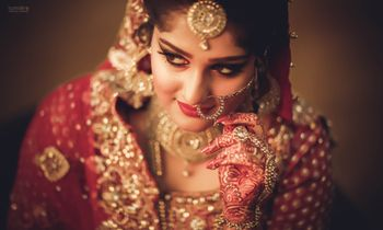 Bridal pose adjusting nath wearing red lehenga