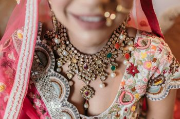 Bride wearing a navaratna necklace with a scalloped blouse.