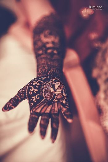 hand mehendi design with bride portrait on palm