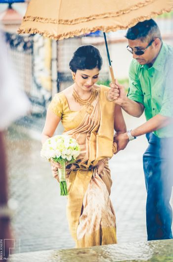 Photo of South Indian bride entering under matching umbrella