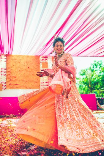 Happy bride twirling in orange lehenga shot