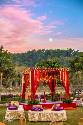 Red and purple theme outdoor mandap decor in the hills