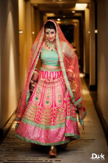Photo of mint and hot pink bridal lehenga