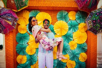Holi party for mehendi with bride and groom against photobooth